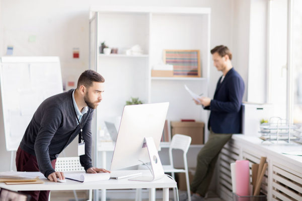 Side view portrait of bearded entrepreneur using computer standing at desk, copy space